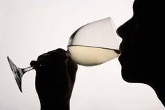 Mostre em silhueta o vinho branco bebendo da mulher Fotos de Stock Royalty Free