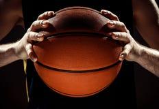 Mostre em silhueta a opinião um jogador de basquetebol que guarda a bola da cesta no fundo preto Imagem de Stock