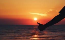 Mostre em silhueta os polegares acima do sinal da mão com praia do nascer do sol Foto de Stock
