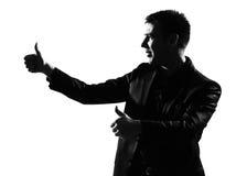 Mostre em silhueta os polegares do vencedor do homem acima Imagens de Stock