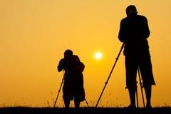 Mostre em silhueta povos da foto do tiro do fotógrafo para um nascer do sol Fotografia de Stock Royalty Free