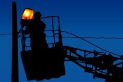 Mostre em silhueta reparos do eletricista em um polo claro no fundo do céu azul Fotos de Stock