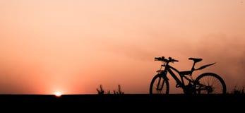 Mostre em silhueta uma bicicleta com fundo crepuscular bonito do céu na borda da estrada Imagem de Stock