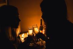 Mostre em silhueta uma imagem de dois vidros do tim-tim das meninas com champanhe Luz da vela Fotografia de Stock Royalty Free