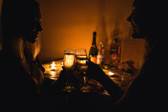 Mostre em silhueta uma imagem de dois vidros do tim-tim das meninas com champanhe Luz da vela Imagem de Stock