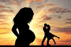 Mostre em silhueta uma mulher gravida e um par loving Imagem de Stock