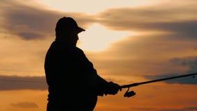 Mostre em silhueta a vara de pesca de jogo do pescador no rio no por do sol da noite do fundo Por do sol bonito da noite durante  vídeos de arquivo
