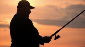 Mostre em silhueta a vara de pesca de jogo do pescador no rio no por do sol da noite do fundo Por do sol bonito da noite durante  video estoque
