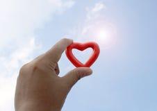 Mostri il cuore rosso sul cielo Fotografia Stock