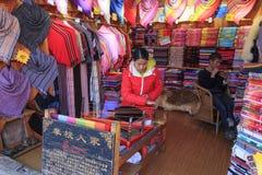 Mosuo kvinna som väver inom hennes whorshop i Lijiang den gamla staden, Yunnan Royaltyfri Bild