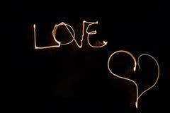 Mot écrit de l'amour dans le ciel dans l'obscurité avec le feu Photo stock