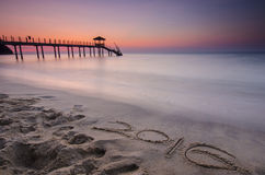 mot 2016 écrit sur le sable et la silhouette du cottage du de pêcheur Photographie stock libre de droits