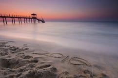 mot 2016 écrit sur le sable et la silhouette du cottage du de pêcheur Images libres de droits