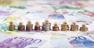 Mot allemand Einkommen sur des piles de pièce de monnaie, fond d'argent liquide Photos stock