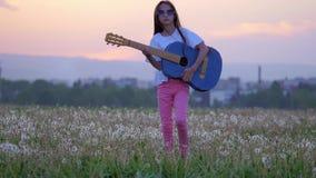 Mot bakgrund av den roliga liten flickamusikern för det stads- landskapet på solglasögon som spelar gitarren och, går i äng av da lager videofilmer