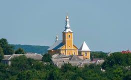 Mot bakgrunden av den blåa himlen kritiserar det kyrkliga tornet med en kupol av guld- rollbesättning i solen med tak av Arkivfoton