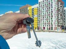 Mot bakgrunden av en modern hyreshus hand med tangenter till lägenheten arkivbild