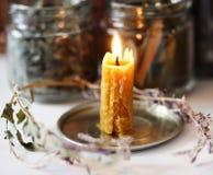 Mot bakgrunden av krus av torkat te är en brinnande stearinljus som ligger runt om torkade blommor och sidor royaltyfri fotografi