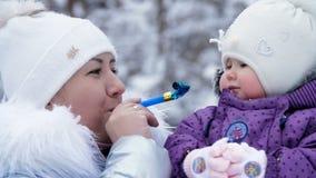 Mot bakgrunden av vinterskogen roar en ung kvinna, mammahåll på hennes händer och engammal dotter lager videofilmer