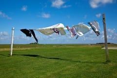mot blå kläder som torkar tvätterit, line skyen Arkivfoto