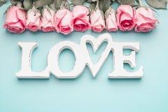 Mot blanc AMOUR avec des roses de rose en pastel sur le fond de bleu de turquoise, vue supérieure Configuration minimale moderne  Photos stock