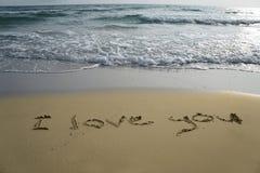 Mot d'écriture je t'aime sur le sable Image stock