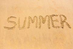 Mot d'été écrit sur le sable de plage Photos stock