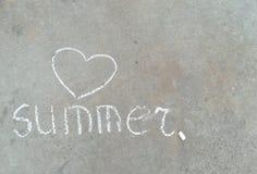 Mot d'été et coeur - dessin blanc de main de craie sur l'asphalte noir photos stock
