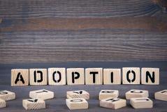 Mot d'adoption écrit sur le bloc en bois Fond en bois foncé avec la texture Photos stock