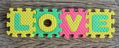 Mot d'amour écrit par puzzle sur le fond en bois Photo stock