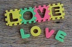 Mot d'amour écrit par puzzle sur le fond en bois Photographie stock