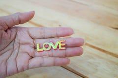 Mot d'amour de prise de main sur le fond en bois Image stock