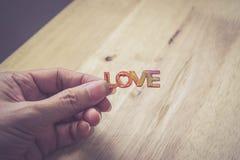 Mot d'amour de prise de main sur le fond en bois Images libres de droits