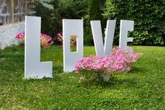Mot d'amour dehors Grandes lettres en plastique blanches sur l'herbe Photo stock