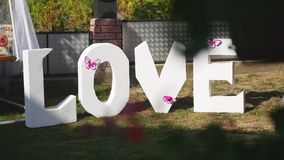 Mot d'amour dehors Le grand plastique blanc marque avec des lettres la décoration de mariage Photos stock