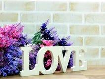 mot d'amour en bois avec la décoration de fleurs artificielles Images libres de droits