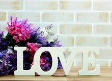 mot d'amour en bois avec la décoration de fleurs artificielles Photos stock