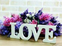 mot d'amour en bois avec la décoration de fleurs artificielles Photo libre de droits