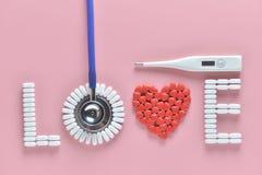 Mot d'AMOUR fait à partir des pilules de médecine, de la forme rouge de coeur et du stéthoscope, la température, sur le fond rose photos stock