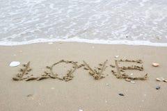 Mot d'amour sur la plage avec la vague Photographie stock