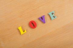 Mot d'AMOUR sur le fond en bois composé des lettres en bois d'ABC de bloc coloré d'alphabet, l'espace de copie pour le texte d'an Photos libres de droits