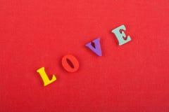Mot d'AMOUR sur le fond rouge composé des lettres en bois d'ABC de bloc coloré d'alphabet, l'espace de copie pour le texte d'anno Images libres de droits