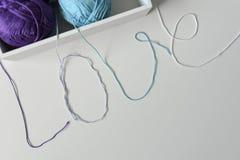 Mot d'amour sur un fond blanc, conçu des fils colorés de laine, boîte avec des boules de fil images stock
