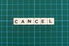 Mot d'annulation fait en mot carré de lettre sur le fond carré vert de tapis photos stock