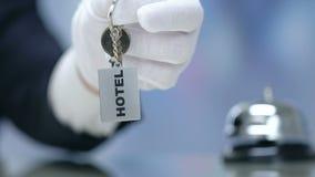 Mot d'hôtel sur le keychain dans la main femelle de concierge, substance amicale, réception banque de vidéos