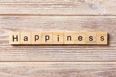 Mot de bonheur écrit sur le bloc en bois Texte de bonheur sur la table, concept Photographie stock