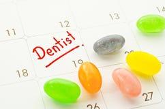 Mot de dentiste dans le calendrier avec la sucrerie colorée photographie stock