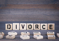 Mot de divorce écrit sur le bloc en bois Fond en bois foncé avec la texture Image stock