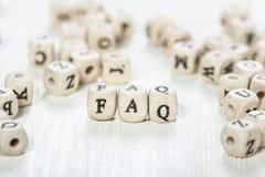 Mot de FAQ écrit sur le bloc en bois Image libre de droits