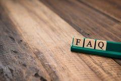 Mot de FAQ sur des tuiles d'alphabet sur la table en bois demandez fréquemment le concept de questions photos libres de droits